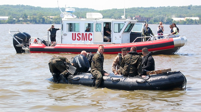 Marines from Marine Corps Systems Command conduct helocasting of the Zodiac F470 near Quantico, Va., while an Open Water Safety Craft floats nearby. The OWSC has been in service since 2006, and is used as an emergency vessel during waterborne training operations. Marine Corps Systems Command is working with Marine Corps Logistics Command and the National Marine Center to refurbish 28 boats in the Corps inventory. (U.S. Marine Corps photo by Jake Feeney)