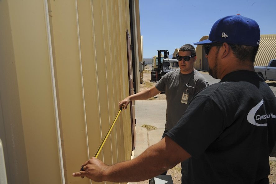 Brodie Carrier and Mark Webber, Consolidated Networks fiber technicians, take measurements for a bracket for a communications cabinet installation at the 309th Aircraft Maintenance and Regeneration Group at Davis-Monthan Air Force Base, Ariz., May 24, 2017. The contractors and 355th Communications Squadron Airmen have been in the process of creating and executing a modification plan, upgrading D-M's network without interfering with any of the Desert Lightning Team's connectivity. (U.S. Air Force photo by Senior Airman Mya M. Crosby)