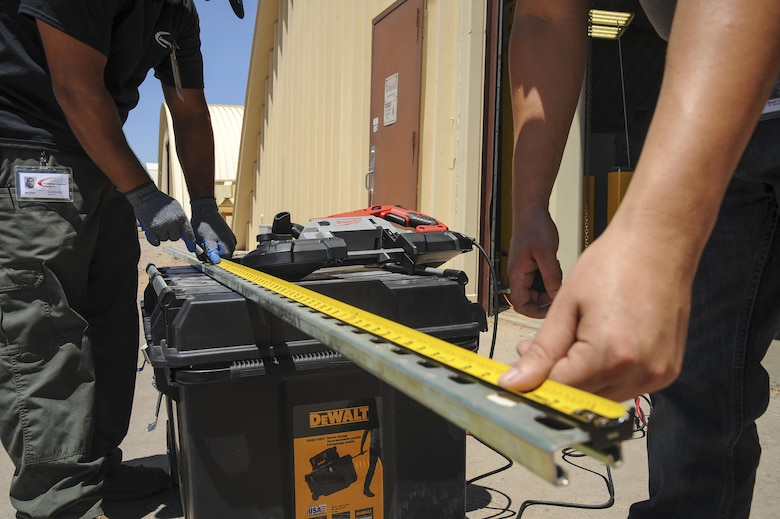 Brodie Carrier and Mark Webber, Consolidated Networks fiber technicians, take measurements for a bracket for a communications cabinet installation at the 309th Aircraft Maintenance and Regeneration Group at Davis-Monthan Air Force Base, Ariz., May 24, 2017. The fiber technicians can reinstall up to two communications cabinets in a day. (U.S. Air Force photo by Senior Airman Mya M. Crosby)