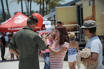 An Eighth Air Force representative hands a child a B-1B Lancer balloon during the Salute to America's Heroes Air and Sea Show in Miami Beach, Fla., May 28, 2017. Members representing all branches of the U.S. Armed Forces took part in the Memorial Day weekend airshow to increase public awareness and understanding of each branch's unique mission and capabilities. (U.S. Air Force photo by Senior Airman Erin Trower)