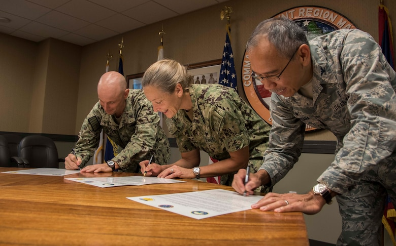From left, U.S. Navy Capt. Hans Sholley, Naval Base Guam commanding officer, U.S. Navy Rear Adm. Shoshana Chatfield, Joint Region Marianas (JRM) commander and U.S. Air Force Col. Joel Almosara, 36th Medical Group commander, sign the Domestic Violence Awareness Month proclamation at JRM headquarters in Asan, Guam, Oct. 2, 2017. Domestic violence is an offense under the United States Code, the Uniform Code of Military Justice and state law. Regulations require military and Department of Defense officials to report any suspicion of family violence. This includes commanders, first sergeants, supervisors, medical personnel and military police. (U.S. Navy photo by JoAnna Delfin)