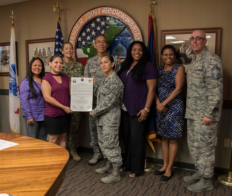 Members with the 36th Medical Group and Joint Region Marianas (JRM) kick off Domestic Violence Awareness month by signing a proclamation at JRM headquarters in Asan, Guam, Oct. 2, 2017. Domestic violence is an offense under the United States Code, the Uniform Code of Military Justice and state law. Regulations require military and Department of Defense officials to report any suspicion of family violence. This includes commanders, first sergeants, supervisors, medical personnel and military police. (U.S. Navy photo by JoAnna Delfin)