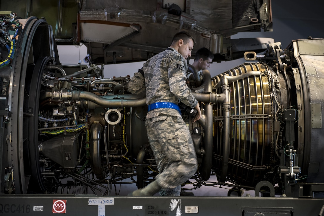 U.S. Air Force Staff Sgt. Kevin Baker, 721st Aircraft Maintenance Squadron quality assurance inspector, inspects the damaged engine of a C-17 Globemaster III at a hangar on Ramstein Air Base, Germany, Oct. 27, 2017. Senior Airman Taylor Corliss, 721st AMXS aerospace propulsion journeyman, right, and his colleagues removed the engine to replace it with an operable one. Baker ensured they completed the job accurately.  (U.S. Air Force photo by Senior Airman Devin Boyer)