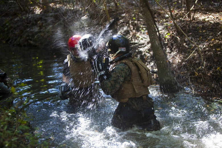 U.S. Marines with the Battalion Landing Team 2nd Battalion, 6th Marine Regiment, 26th Marine Expeditionary Unit (MEU), execute knife techniques against each other during a simulated bout in a creek during a Martial Arts Instructor Course (MAIC) at Marine Corps Base Camp Lejeune, N.C., Oct. 26, 2017.