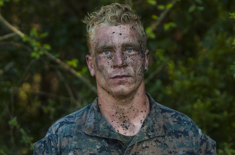 U.S. Marine Corps Cpl. Alois Scott, a machine gunner with the Battalion Landing Team 2nd Battalion, 6th Marine Regiment, 26th Marine Expeditionary Unit (MEU), stands cover in mud and debris after completing the final event of a Martial Arts Instructor Course (MAIC) at Marine Corps Base Camp Lejeune, N.C., Oct. 26, 2017.