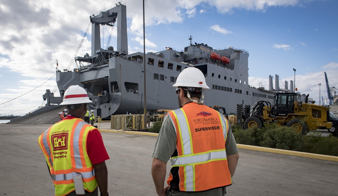 Dennis Davis, left, U.S. Army Corps of Engineers, Charleston District transportation management specialist and Jason Metts, right, Cooper Ports America International Longshoremen's Association superintendent, look on as the USNS Brittin (T-AKR-305) with 855 pieces of equipment Oct. 28, 2017, at Joint Base Charleston-Weapons Station, S.C.