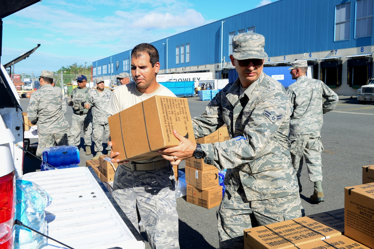 A line of airmen load boxes into the back of a car.