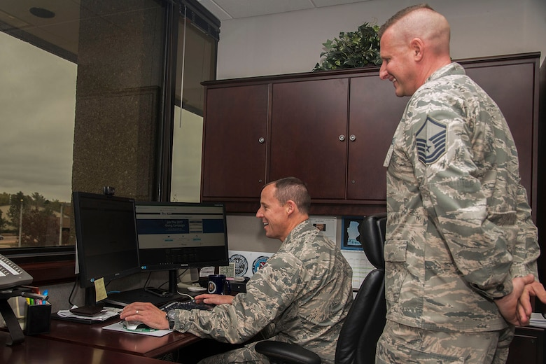 Master Sgt. Jason Gregory, 21st Civil Engineer Squadron noncommissioned officer in charge of requisitions and optimization, and installation project officer for the Combined Federal Campaign, assists Col. Todd Moore, 21st Space Wing commander, in making his commitment to CFC online, Oct. 30, 2017 at Peterson Air Force Base, Colorado.