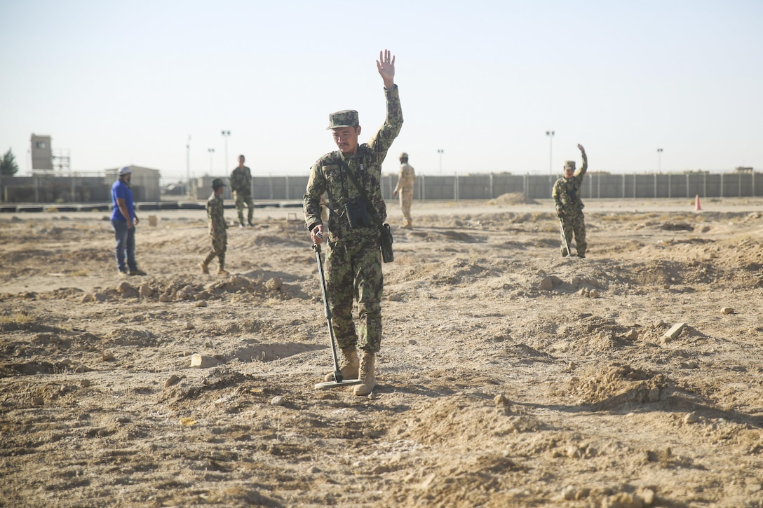Afghan National Army soldiers with 215th Corps signal to halt after noticing indicators of a notional improvised explosive device during a mine sweeping simulation at Camp Shorabak, Afghanistan, Oct. 29, 2017. U.S. advisors are leading an eight-week route clearance course with approximately 40 engineer soldiers from various brigades within 215th Corps. The soldiers learn both mounted and dismounted clearance procedures and the basics of countering IEDs, allowing for enhanced mobility of 215th Corps throughout Helmand province during combat and security operations. (U.S. Marine Corps photo by Sgt. Lucas Hopkins)
