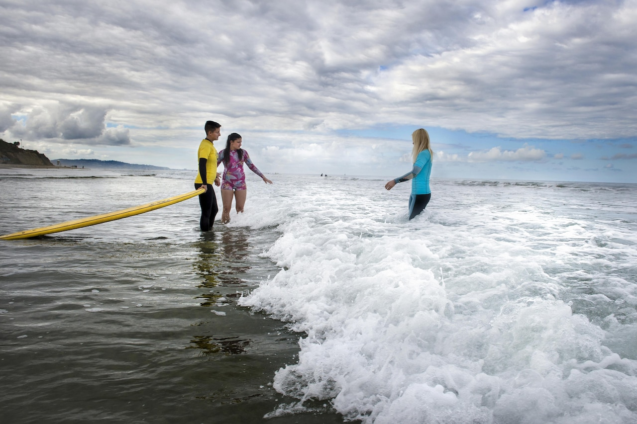 A surfer is assisted by a volunteer as she enters the water to meet a surfing instructor.