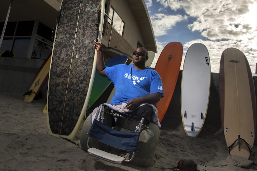 A double amputee surfer poses with his surfboard.