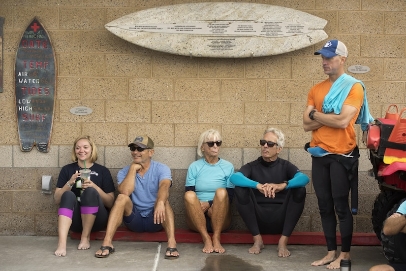 Volunteers stand and squat against a wall while listening to a brief before a surf therapy session.