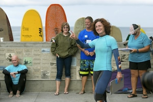 A program manager points out safety measures while standing with a group of surfers.