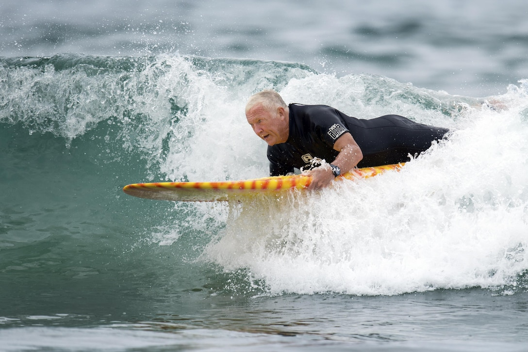 A surfer rides a wave on a surfboard.