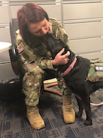 Army Master Sgt. Leigh Michel gets a kiss from her service dog, Lizzy