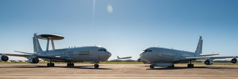 An E-3 Sentry AWACS from the 964th Airborne Air Control Squadron (AACS), 552nd Air Control Wing (ACW), Tinker Air Force Base (AFB), Oklahoma, sits on the flightline next to an E-8C Joint STARS from Team JSTARS as an E-8C Joint STARS aircraft passes in the background at Robins AFB, Ga, Oct. 26, 2017.