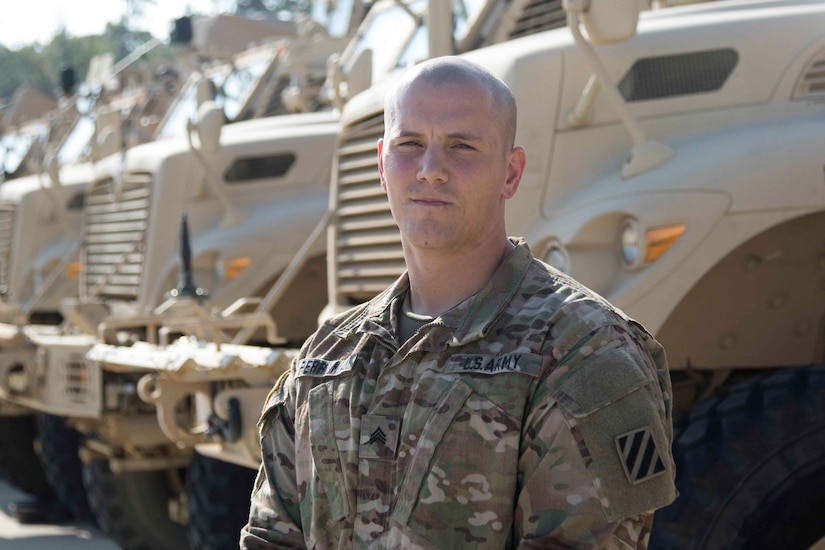 Soldier poses in front of military vehicles.