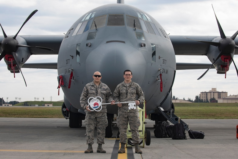 Staff Sgt. James Duncan and Senior Airman Ian Hall, both from the 374th Aircraft Maintenance Squadron crew chiefs, pose for a photo in front of a C-130J Super Hercules at Yokota Air Base,  Japan, Oct. 31, 2017. This is the sixth C-130J delivered to Yokota and the first from Dyess Air Force Base, Texas, as part of fleet-wide redistribution of assets set in motion by Air Mobility Command.