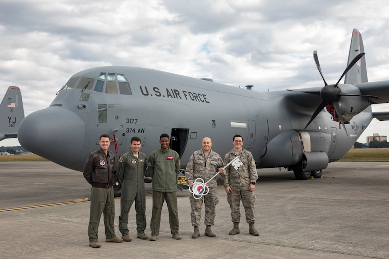 Members of the C-130J delivery team pose for a photo in front of a C-130J Super Hercules at Yokota Air Base, Japan, Oct. 31, 2107. This is the sixth C-130J delivered to Yokota and the first from Dyess Air Force Base, Texas, as part of fleet-wide redistribution of assets set in motion by Air Mobility Command.