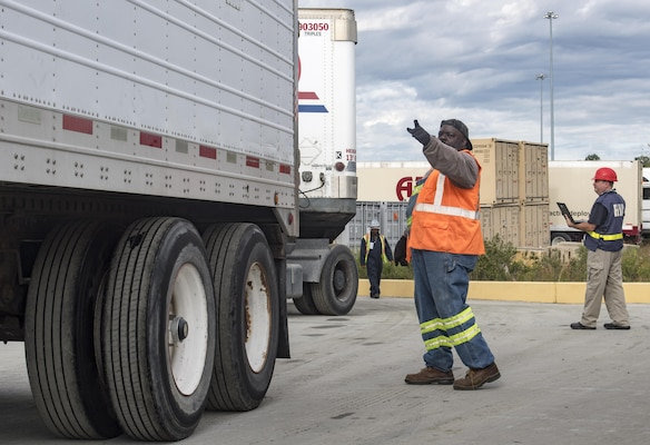 A longshoreman directs a truck onto the USNS Brittin (T-AKR-305) Oct. 29, 2017, at Joint Base Charleston-Weapons Station, S.C. As the first shipment makes its way through the Atlantic Ocean, FEMA's cargo receiving efforts continue at the installation support base here in preparation for future sealifts. As the recovery efforts continue, the deliveries will begin to shift from essentials to the equipment and supplies required to rebuild the damaged infrastructure.