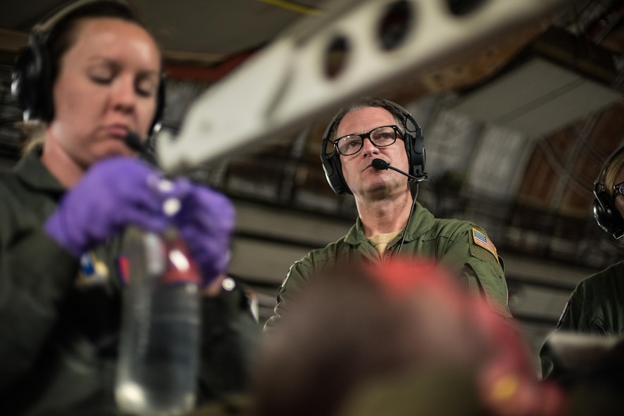 Maj. Casey Patton, medical crew coordinator for the flight and senior health technician at the 137th Aeromedical Evacuation Squadron, Will Rogers Air National Guard Base, Oklahoma City, listens to a crew member through his headset as another aeromedical technician hangs an IV fluid bag while transporting simulated burn patients aboard a C-17 Globemaster III from the 105th Airlift Wing, Stewart Air National Guard Base, N.Y., en route to Altus Air Force Base, Altus, Okla., Oct. 30, 2017. The flight was part of a wildfire scenario during Vigilant Guard, a North American Command-sponsored, state-wide emergency response exercise held Oct. 30 to Nov. 2, 2017. (U.S. Air National Guard photo by Staff Sgt. Kasey M. Phipps)