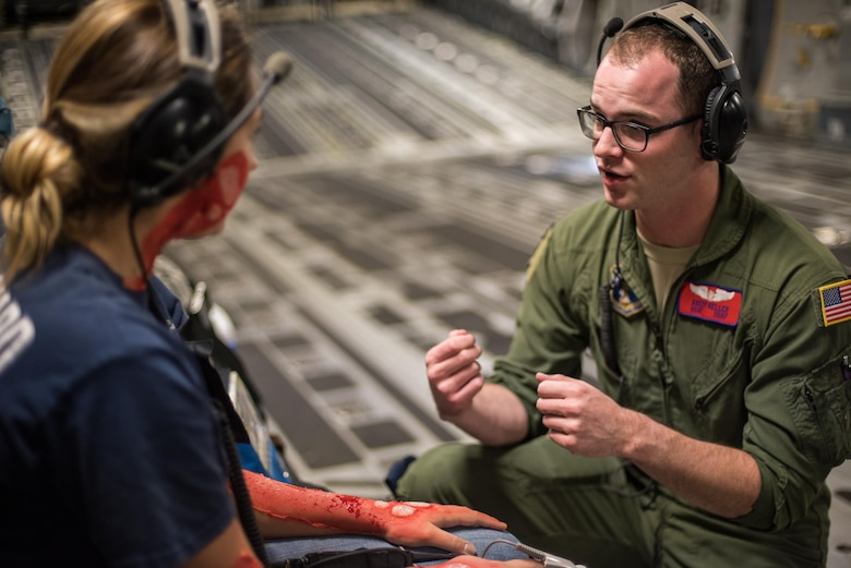 Staff Sgt. Avery Keller, aeromedical evacuation technician from the 137th Aeromedical Evacuation Squadron, Will Rogers Air National Guard Base, Oklahoma City, measures the heart rate of a simulated burn victim, Senior Airman Ashleigh Duncan from the 137th Special Operations Logistics Readiness Squadron, while transporting simulated patients aboard a C-17 Globemaster III from the 105th Airlift Wing, Stewart Air National Guard Base, N.Y., en route to Altus Air Force Base, Altus, Okla., Oct. 30, 2017. The flight was part of a wildfire scenario during Vigilant Guard, a North American Command-sponsored, state-wide emergency response exercise held Oct. 30 to Nov. 2, 2017. (U.S. Air National Guard photo by Staff Sgt. Kasey M. Phipps)