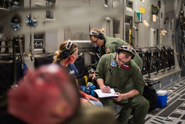 Staff Sgt. Avery Keller, an aeromedical evacuation technician from the 137th Aeromedical Evacuation Squadron, Will Rogers Air National Guard Base, Oklahoma City, completes medical documentation for a simulated burn patient, Senior Airman Ashleigh Duncan from the 137th Special Operations Logistics Readiness Squadron, while transporting patients with burn moulage aboard a C-17 Globemaster III from the 105th Airlift Wing, Stewart Air National Guard Base, N.Y., en route to Altus Air Force Base, Altus, Okla., Oct. 30, 2017. The flight was part of a wildfire scenario during Vigilant Guard, a North American Command-sponsored, state-wide emergency response exercise held Oct. 30 to Nov. 2, 2017. (U.S. Air National Guard photo by Staff Sgt. Kasey M. Phipps)