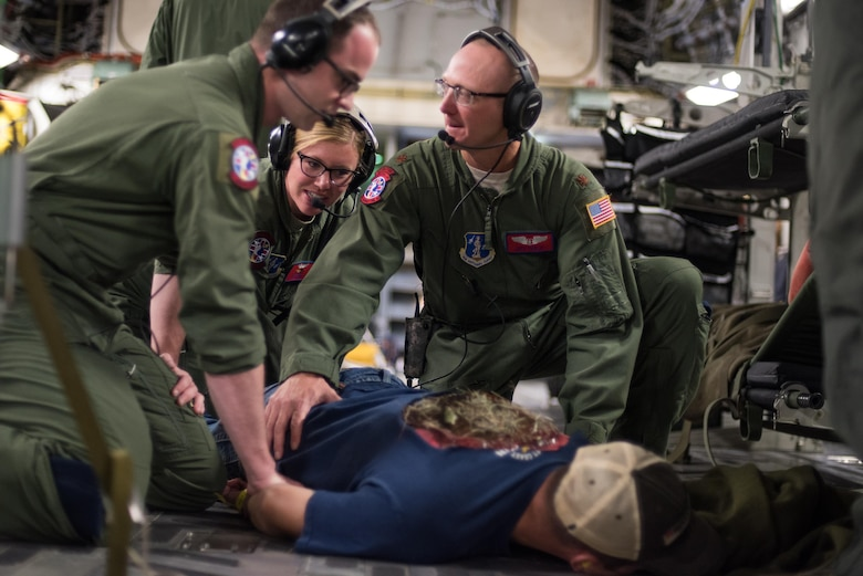 Staff Sgt. Avery Keller (front), second aeromedical evacuation technician, Staff Sgt. Sarah Bell (middle), charge medical technician, and Maj. Jeff Barley (right), medical crew director, all from the 137th Aeromedical Evacuation Squadron, Will Rogers Air National Guard Base, Oklahoma City, restrain a simulated patient, Senior Airman Andrew Dyer, 137th Special Operations Logistics Readiness Squadron from the same base, as he acts out an escape scenario during patient transportation aboard a C-17 Globemaster III from the 105th Airlift Wing, Stewart Air National Guard Base, N.Y., en route to Altus Air Force Base, Altus, Okla., Oct. 30, 2017. The flight was part of a wildfire scenario during Vigilant Guard, a North American Command-sponsored, state-wide emergency response exercise held Oct. 30 to Nov. 2, 2017. (U.S. Air National Guard photo by Staff Sgt. Kasey M. Phipps)