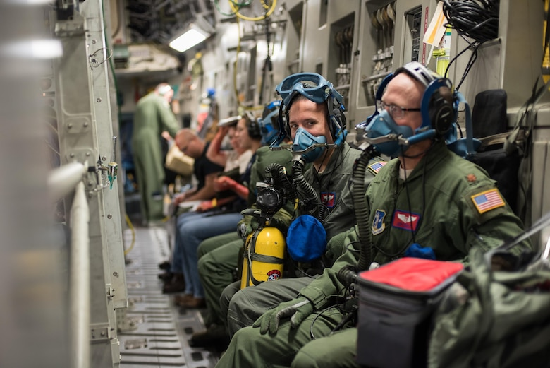 Capt. Sam Lingle (left), flight nurse, and Maj. Jeff Barley (right), medical crew director, both from the 137th Aeromedical Evacuation Squadron at Will Rogers Air National Guard Base, Oklahoma City, don oxygen masks during a simulated in-flight emergency while transporting patients aboard a C-17 Globemaster III from the 105th Airlift Wing, Steward Stewart Air National Guard Base, N.Y., en route to Altus Air Force Base, Altus, Okla., Oct. 30, 2017. The flight was part of a wildfire scenario during Vigilant Guard, a North American Command-sponsored, state-wide emergency response exercise held Oct. 30 to Nov. 2, 2017. (U.S. Air National Guard photo by Staff Sgt. Kasey M. Phipps)