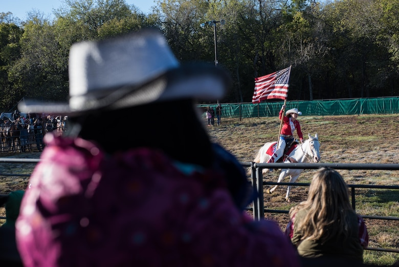 Kate Gibson, 2017 89ers Day Rodeo Princess, presents the U.S. Flag during the National Anthem at the opening of the 6th Annual Oklahoma National Guard Adjutant General's Horseback Heroes event, Oct. 28, 2017, at Covey Creek Ranch in Oklahoma City. Horseback Heroes is conducted each fall for military children to show support to the families of Guardsmen, especially those who are deployed. (U.S. Air National Guard photo by Staff Sgt. Kasey M. Phipps/Released)