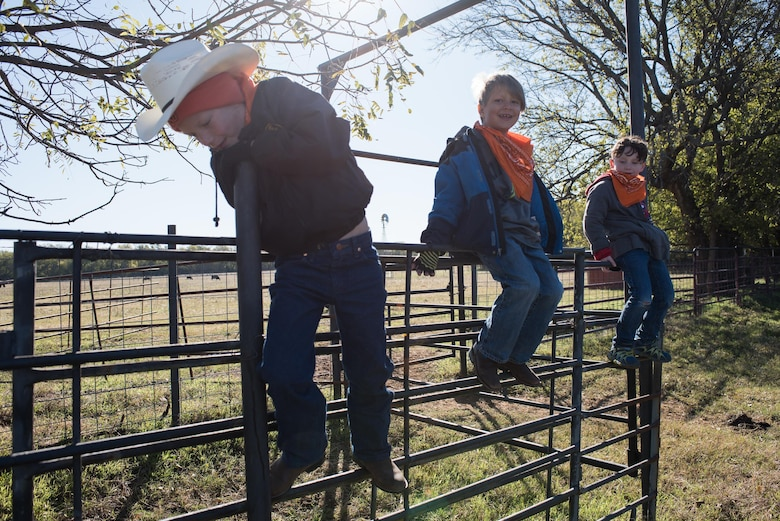 Children climb the fence of a horse pen while waiting for their next activity station at the 6th Annual Oklahoma National Guard Adjutant General's Horseback Heroes event, Oct. 28, 2017, at Covey Creek Ranch in Oklahoma City. Horseback Heroes is conducted each fall for military children to show support to the families of Guardsmen, especially those who are deployed. (U.S. Air National Guard photo by Staff Sgt. Kasey M. Phipps/Released)