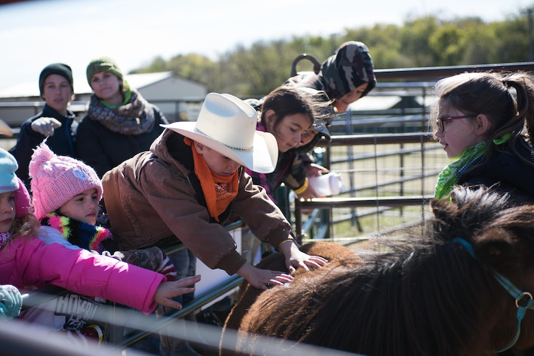 Children stretch over a fence to pet Brighty, a pony at the petting area hosted by the 4H Club, at the 6th Annual Oklahoma National Guard Adjutant General's Horseback Heroes event, Oct. 28, 2017, at Covey Creek Ranch in Oklahoma City. Horseback Heroes is conducted each fall for military children to show support to the families of Guardsmen, especially those who are deployed. (U.S. Air National Guard photo by Staff Sgt. Kasey M. Phipps/Released)