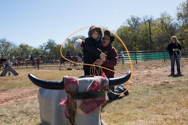A roping instructor demonstrates proper roping techniques to a child at the 6th Annual Oklahoma National Guard Adjutant General's Horseback Heroes event, Oct. 28, 2017, at Covey Creek Ranch in Oklahoma City. Horseback Heroes is conducted each fall for military children to show support to the families of Guardsmen, especially those who are deployed. (U.S. Air National Guard photo by Staff Sgt. Kasey M. Phipps/Released)