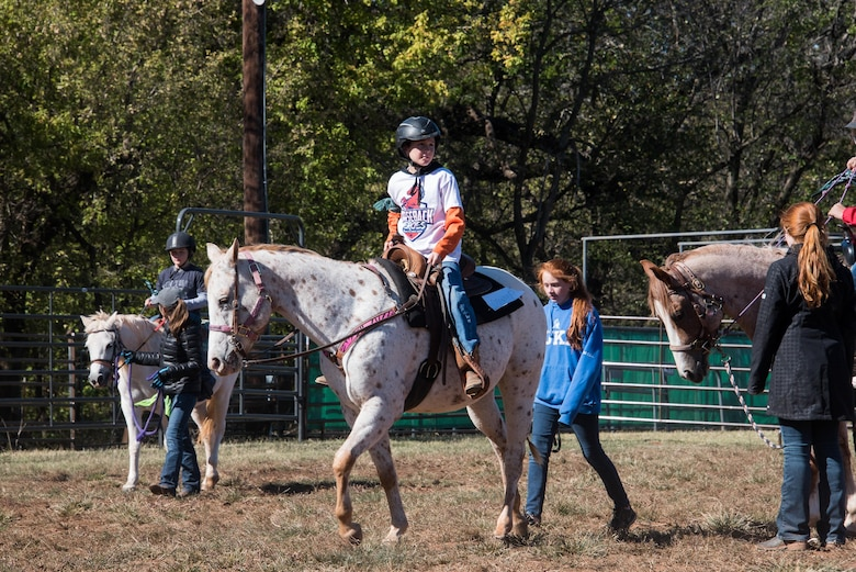 A child guides a horse around an arena during the 6th Annual Oklahoma National Guard Adjutant General's Horseback Heroes event, Oct. 28, 2017, at Covey Creek Ranch in Oklahoma City. Horseback Heroes is conducted each fall for military children to show support to the families of Guardsmen, especially those who are deployed. (U.S. Air National Guard photo by Senior Airman Brigette Waltermire/Released)