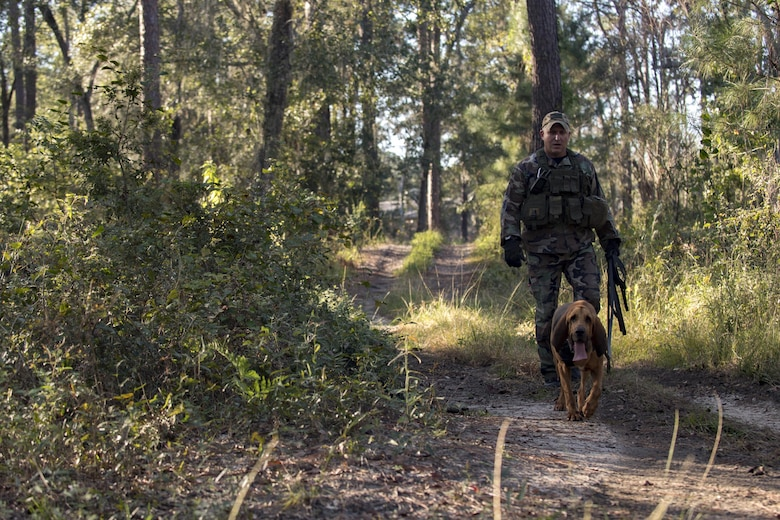 Anthony Catlett, officer from Lowndes County Sheriff's Office, and K9 Lucius, search for Airmen during evasion training, Oct. 24, 2017, at Moody Air Force Base, Ga. The new, three-day combined training is designed to merge many smaller courses and seamlessly tie together skills that could be used in the event that Airmen become isolated during a mission. (U.S. Air Force photo by Senior Airman Daniel Snider)