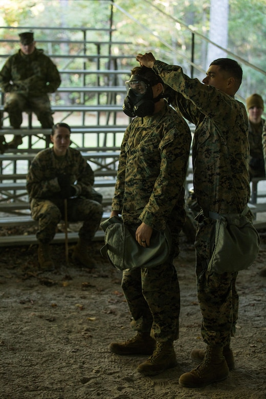 U.S. Marine Corps Cpl. David Mendez, right, a chemical, biological, radiological, nuclear defense specialist with the 26th Marine Expeditionary Unit (MEU), demonstrates the proper fitting of an M50 Joint Service General Purpose Mask during a CBRN training event at Marine Corps Base Camp Lejeune, N.C., Oct. 30, 2017.