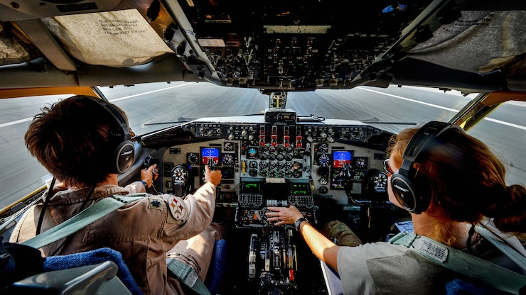 Two pilots operate controls in a cockpit.