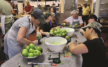 Volunteers peel, core and slice pounds of Granny Smith apples during one of the Historical and Archaeological Society of Fort Riley apple pie making shifts at the Culinary Lab Sept. 19. This one of the few stations in the apple pie making process.