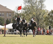 Members of the Commanding General's Mounted Color Guard complete a group jump during a demonstration at Fall Apple Day Sept. 23.