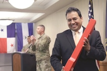 Carlos Gomez, president and CEO of the Hispanic Chamber of Commerce of Greater Kansas City, smiles after receiving a wooden Big Red One as a gift for being the keynote speaker during a Hispanic Heritage Month observance at Riley's Conference Center on Fort Riley Sept. 20.