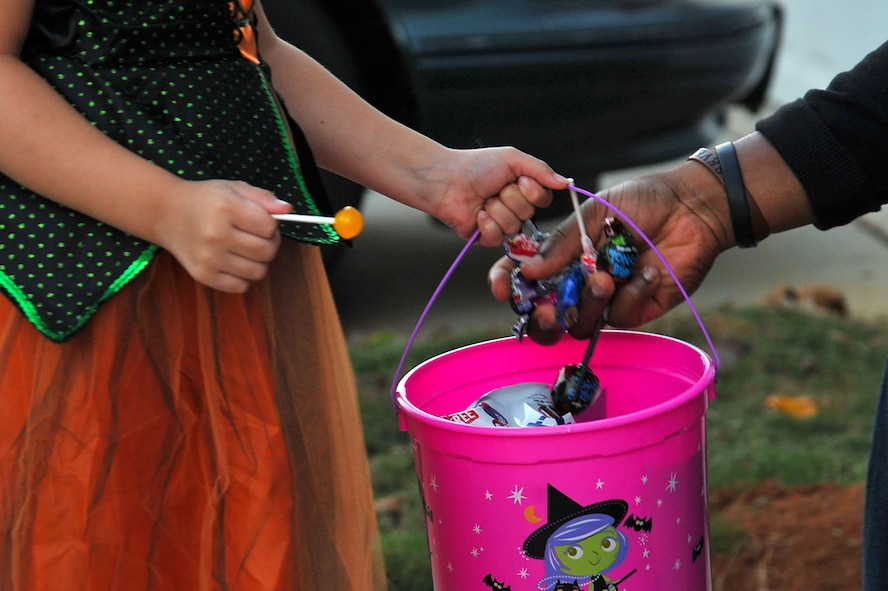A base resident places candy in a child's bucket during trick-or-treating at Shaw Air Force Base, South Carolina, Oct. 31, 2017.