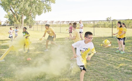 Fifth-grade teachers douse their students in powdered paint during the Dragon Dash Sept. 22 at Seitz Elementary School. The annual color run encourages students and parents alike to live a healthy lifestyle while having fun.