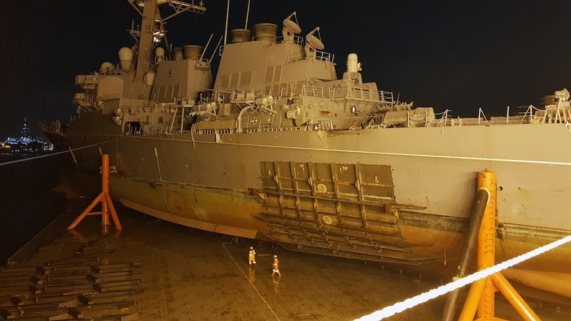 The guided missile destroyer USS John S. McCain sits on heavy lift transport MV Treasure in Changi, Singapore.