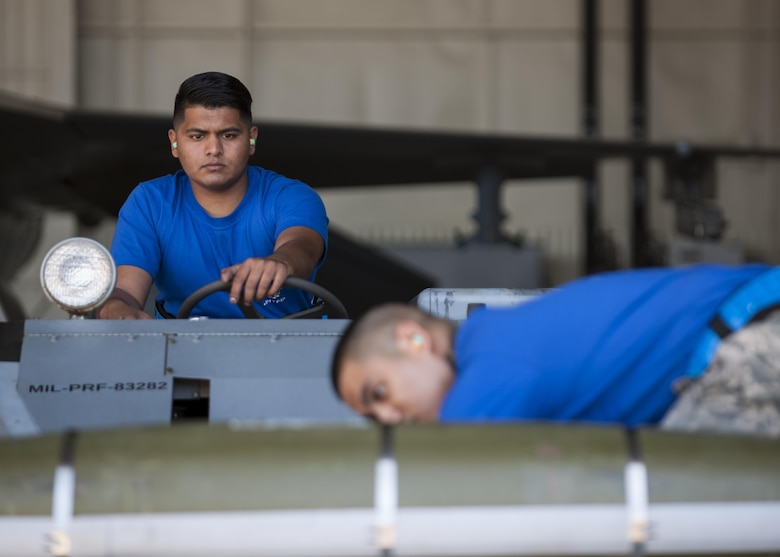 U.S. Air Force Senior Airman Shivanand Bissoon, and Staff Sgt. Princeleo Pecjo, 35th Air Munitions Squadron weapons load crew members, participate in a weapons load competition at Kunsan Air Base, Republic of Korea, Oct. 20, 2017. Load competitions showcase the skills and abilities of each Aircraft Maintenance Unit and prepare teams to load munitions as expeditiously and safely as possible to support Pacific Command priorities on the Korean Peninsula and within the region. (U.S. Air Force photo by Staff Sgt. Victoria H. Taylor)