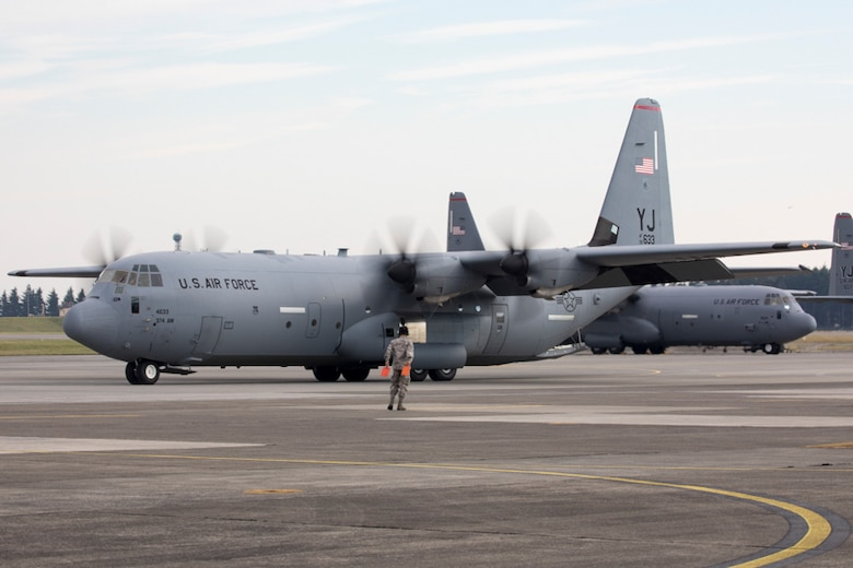 A crew chief from the 374th Aircraft Maintenance Squadron marshals a C-130J Super Hercules aircraft at Yokota Air Base, Japan, Nov.1, 2017.