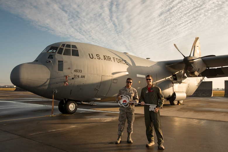 Staff Sgt. Rembert Dash, 374th Aircraft Maintenance Squadron crew chief, and Maj. George Metros, 36th Airlift Squadron C-130J instructor pilot, hold the ceremonial key in front of a C-130J Super Hercules at Yokota Air Base, Japan, Nov. 3, 2017.