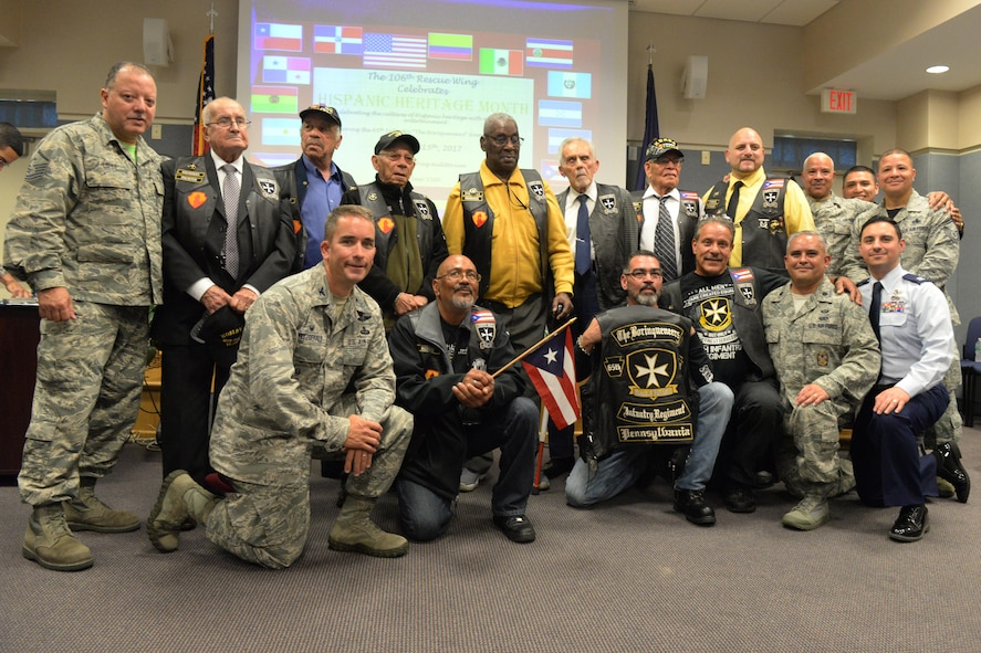 Members of the 106th Rescue Wing stand with the Borinqueneers for a group photo during the Hispanic Heritage Month celebration at New York Air National Guard's 106th Rescue Wing in Westhampton Beach, New York on October 15, 2017. The event honored the Borinqueneers, the U.S. Army's 65th Infantry Regiment made up by the U.S. Territory of Puerto Rico, who served during both World Wars and the Korean War. (U.S. Air National Guard photo by Airman 1st Class Daniel H. Farrell)