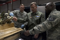 U.S. Air Force Gen. Tod D. Wolters, U.S. Air Forces in Europe and Air Forces Africa commander, tests a piece of equipment for cracks with Tech. Sgt. James Cone and Staff Sgt. Timothy J. Schwenning II, both 86th Maintenance Squadron Nondestructive Inspection technicians, during an immersion tour on Ramstein Air Base, Germany, Oct. 23, 2017. Wolters coined all four Airmen assigned to the shop for their efforts in finding the best course of action for detecting cracks in the equipment saving the Air Force money. (U.S. Air Force photo by Senior Airman Tryphena Mayhugh)