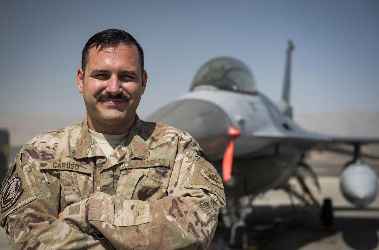 Airman poses for a photo in front of an F-16 fighter jet.