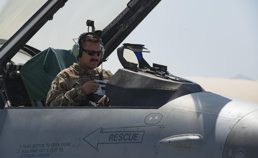 Airman sits in F-16 fighter jet cockpit to check equipment.
